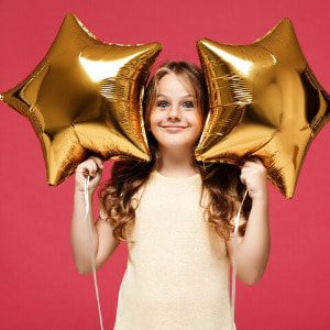 A smiling girl celebrating with golden star balloons