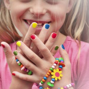 Happy little girl showing her colorful non toxic nail polish
