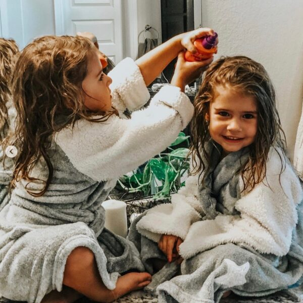 little sisters applying rock the lock curl boost to each other