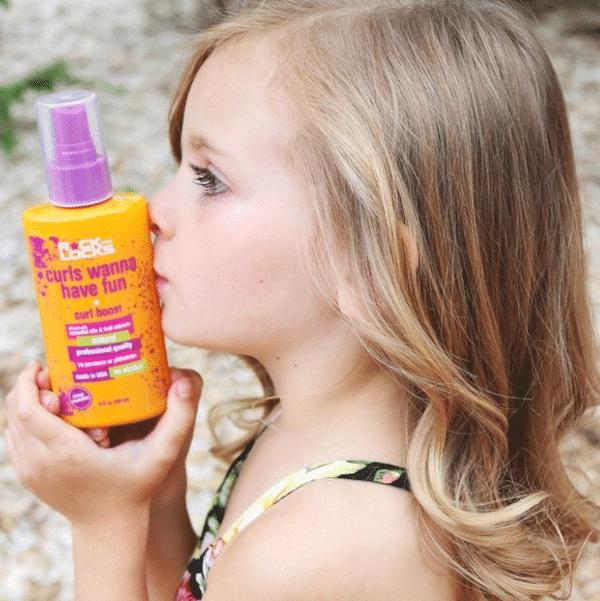 little girl kissing curl boost bottle